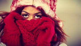 Mulatto woman wearing warm winter clothing, closeup. Winter clothing, fashion concept. Closeup of young mulatto woman covering her face with hands wearing gloves Stock Images
