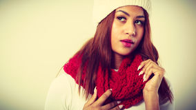 Mulatto woman wearing warm winter clothing. Winter clothing, fashion concept. Beautiful young mulatto woman wearing red woolen scarf white cap. Mixed race girl Royalty Free Stock Photo