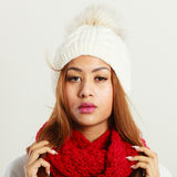 Mulatto woman wearing warm winter clothing. Winter clothing, fashion concept. Beautiful young mulatto woman wearing red woolen scarf white cap. Mixed race girl Stock Photography