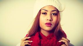 Mulatto woman wearing warm winter clothing. Winter clothing, fashion concept. Beautiful young mulatto woman wearing red woolen scarf white cap. Mixed race girl Stock Photo