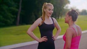 Mulatvrouw die met blondemeisje spreekt Vrouwelijke vrienden die in park bij de zomer spreken stock footage