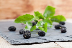 Mulberries in a basket. Black mulberries spilt on a slate board. Shallow dof Stock Image