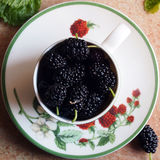 Mulberries in a cup. Mulberries in a ceramic cup , decorated with raspberries paintings Stock Images