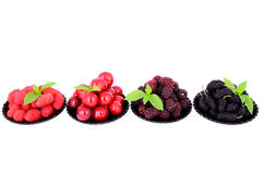 Mulberry, cherry, raspberry, blackberry in a plates. Isolated on white, decorated with green leaves Royalty Free Stock Image
