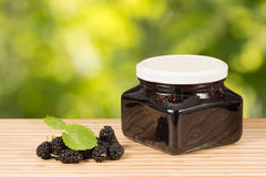 Mulberry jam in jar and some fresh fruits and leaves on table green leaves background. Stock Photos