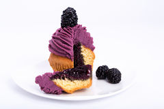 Mulberry sweet cupcake cut with a berry on the top on a white background. Stock Images
