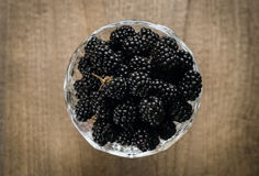 Mulberry in a vase on wooden table, top view Royalty Free Stock Photos
