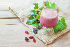 Mulberry Yogurt Smoothie. A glass of mulberry yogurt smoothie, a beautiful booster smoothie, on burlap and wood background stock photos
