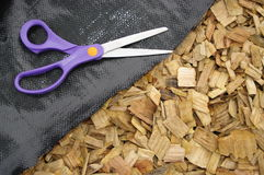 Mulch and weedmatt and scissors stock photography