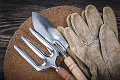 Mulching fiber hand spade trowel fork safety gloves on wooden bo Stock Image