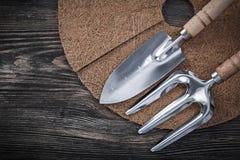 Mulching mat shovel trowel fork on wood board gardening concept Royalty Free Stock Photos