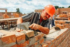Man puts a brick. MULCHYCI, Rivne / UKRAINE - JUNE 22 2011: Man puts a brick in the construction Stock Photography