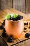 Mule de Blackberry Moscou dans la tasse de cuivre sur le fond rustique photographie stock