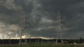 Mulen stormig himmel mot elkraftpyloner av överföringslinjen stock video