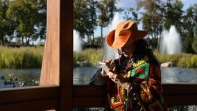 Mulher à moda adulta em um chapéu de vaqueiro à moda e em um multi poncho colorido filme