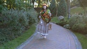Mulher à moda adulta em um chapéu de vaqueiro à moda e em um multi poncho colorido vídeos de arquivo