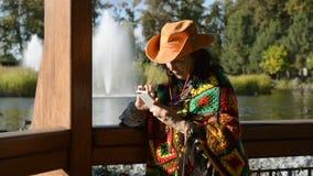 Mulher à moda adulta em um chapéu de vaqueiro à moda e em um multi poncho colorido video estoque