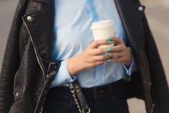 Mulher à moda com tratamento de mãos colorido no casaco de cabedal que realiza nas mãos um a xícara de café de papel Imagens de Stock
