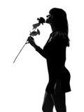 A mulher à moda da silhueta que cheira uma flor levantou-se Fotos de Stock Royalty Free