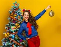 Mulher à moda de sorriso que mostra a bola do Natal Fotografia de Stock Royalty Free