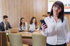 Mulher à moda do trabalhador de escritório nos vidros com o telefone nas mãos contra o fundo de colegas de trabalho imagem de stock