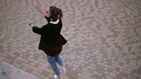 Mulher à moda feliz com o rabo de cavalo que vai abaixo das escadas playfully no parque Girar e dançar com música nela video estoque