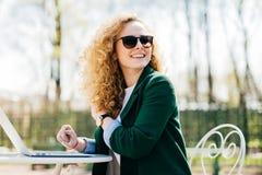 Mulher à moda feliz com os óculos de sol vestindo do cabelo leve encaracolado que trabalham com portátil fora no parque que datil fotos de stock