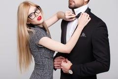 Mulher à moda loura com curva vermelha do laço dos bordos para o homem no smoking foto de stock