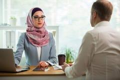 Mulher à moda no hijab que faz a conversação na mesa com homem foto de stock