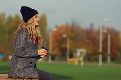 Mulher à moda nova com café em um parque Fotografia de Stock Royalty Free