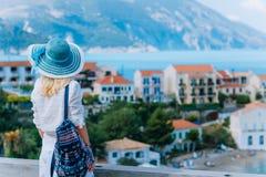 Mulher à moda nova do viajante que aprecia a vista da vila tranquilo colorida de Assos Modelo fêmea que veste o sunhat azul, bran foto de stock royalty free