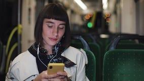 Mulher à moda nova nos fones de ouvido que escuta a música e que consulta no telefone celular que monta em público o transporte c vídeos de arquivo