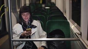Mulher à moda nova nos fones de ouvido que escuta a música e que consulta no telefone celular que monta em público o transporte c filme