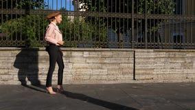 Mulher à moda nova que anda nos saltos na rua da cidade vídeos de arquivo