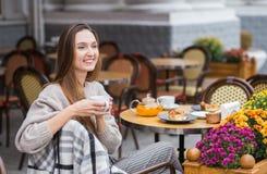 Mulher à moda nova que come um café da manhã francês com o café e o bolo que sentam-se no terraço do café fotografia de stock royalty free