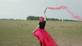 Mulher à moda que anda através do campo com bomba de fumo filme