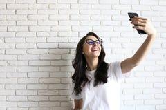 Mulher à moda que faz o selfie com o saco de compras no fundo amarelo da parede Venda do feriado de inverno imagem de stock