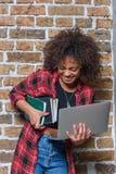 Mulher à moda que sorri ao guardar o portátil e os cadernos Foto de Stock