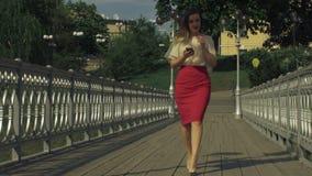 Mulher à moda que usa o telefone esperto app na ponte da cidade filme