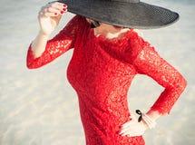 Mulher à moda que veste o vestido e o chapéu negro vermelhos Fotografia de Stock