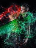 A mulher à rapaz na água vermelha e verde espirra foto de stock
