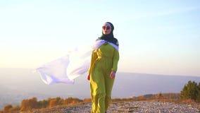Mulher árabe à moda no hijab e vestido longo no forte vento vídeos de arquivo
