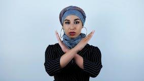 Mulher árabe bonita nova que mantém suas mãos cruzadas e que agita sua cabeça que rejeita no fundo branco isolado filme