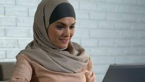 Mulher árabe bonita que datilografa no PC do portátil, conversando no app em linha das redes sociais filme