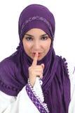 Mulher árabe bonita que pede o silêncio com o dedo nos bordos Imagens de Stock