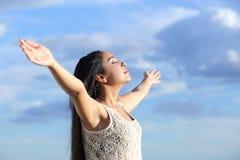 Mulher árabe bonita que respira o ar fresco com braços aumentados