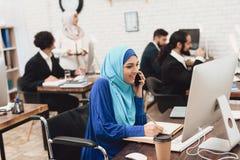 Mulher árabe deficiente na cadeira de rodas que trabalha no escritório A mulher está trabalhando no computador de secretária e es imagens de stock