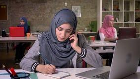A mulher árabe deleitada está no telefone, escutando e escrevendo notas abaixo do quando que está em seu desktop, negócio árabe video estoque