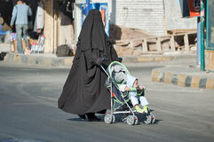 A mulher árabe no hijab conduz o transporte com criança Fotografia de Stock
