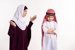 A mulher árabe no hijab discute o menino no keffiyeh foto de stock